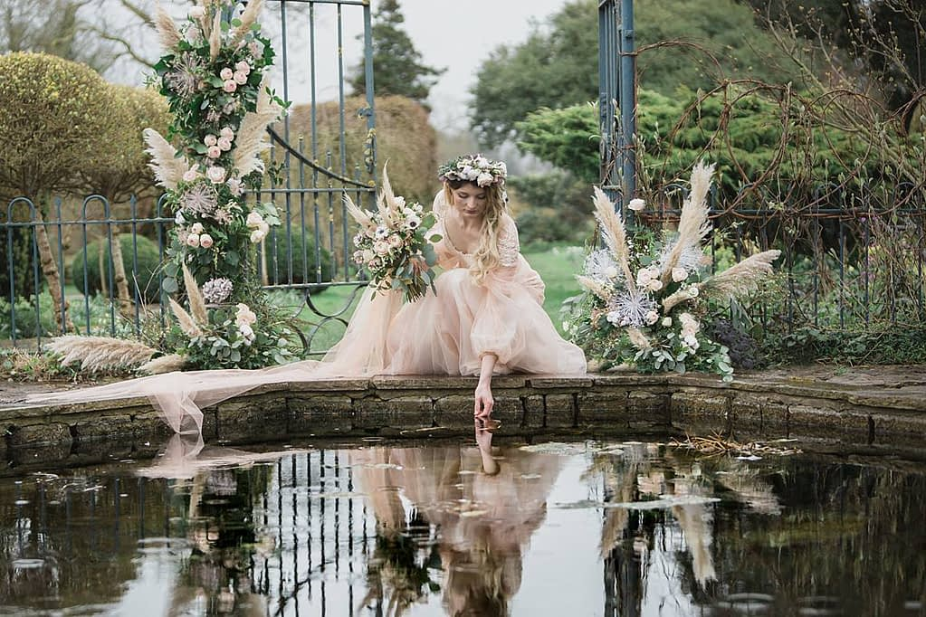 Barnsley House bride touching water for wedding photographer