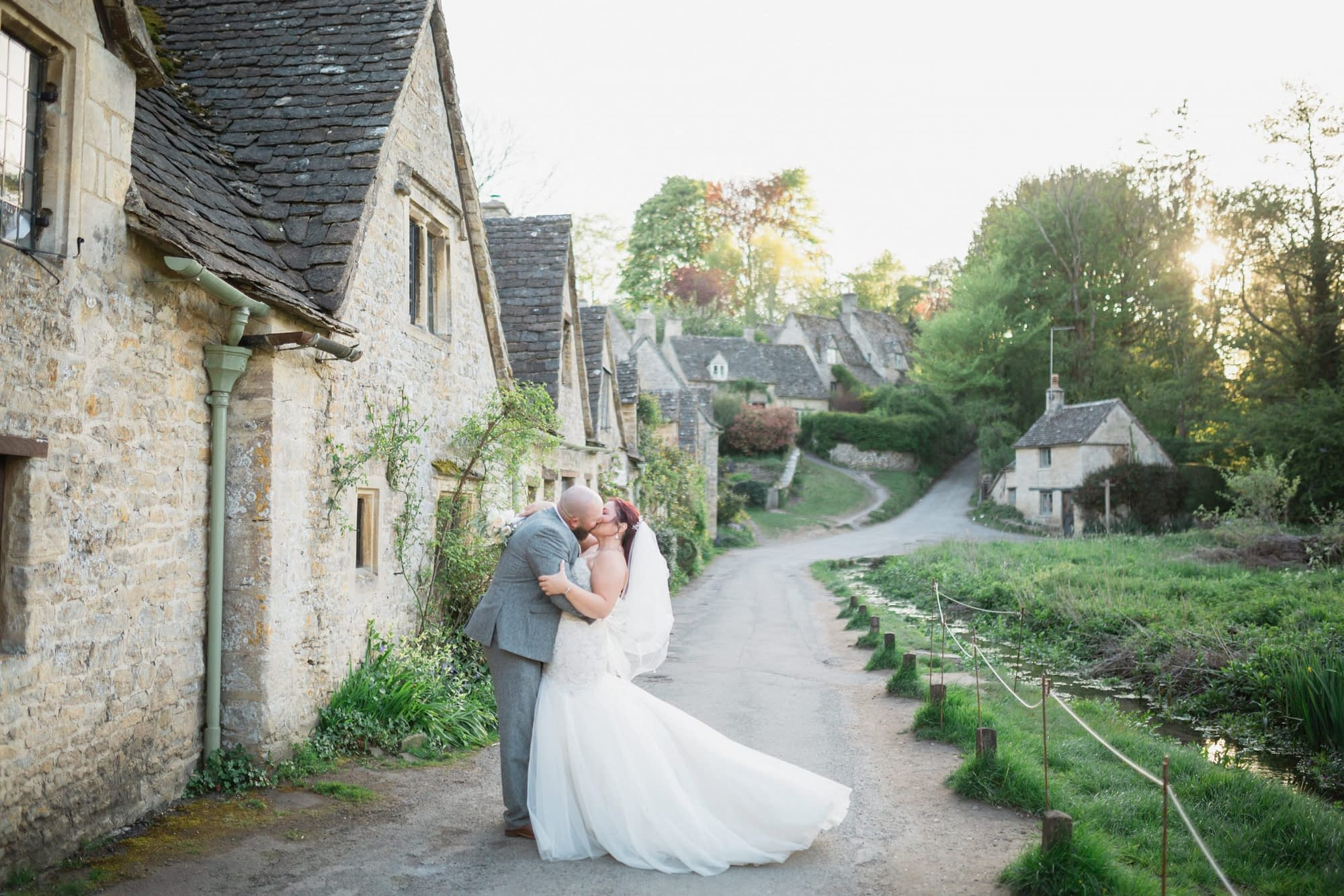 couple kissing in bibury cotswold wedding