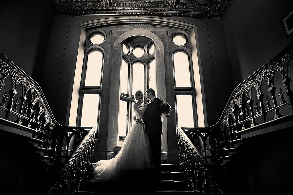 couple standing at the top of the gran Grittleton house staircase for wedding photographer