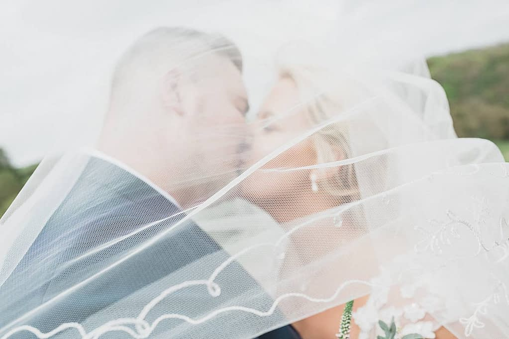 couple kissing under veil Kingscote Barn wedding photographers