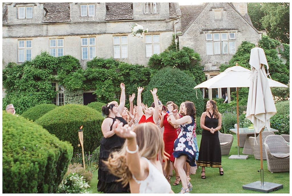 bride throwing bouquet Barnsley House photographer