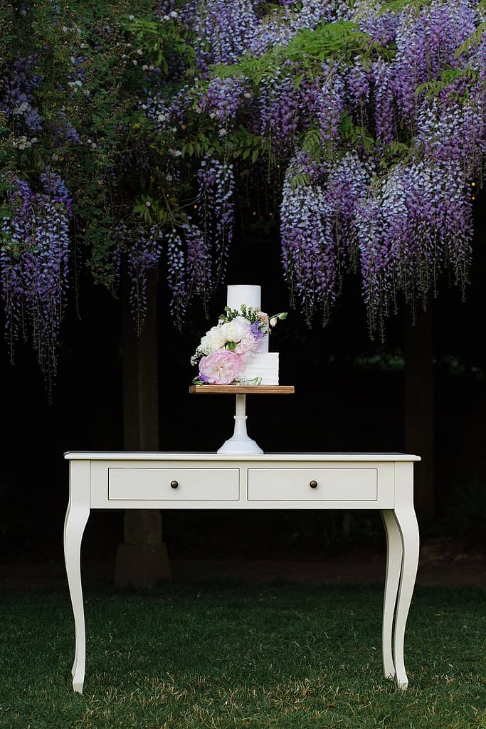 wedding cake sitting on trestle table with wisteria behind cake