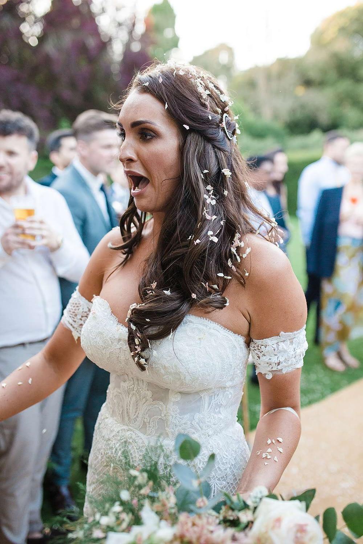 bride covered in confetti wedding photographer uk