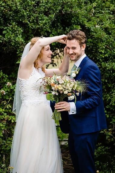 micro wedding photographer fixing flower to groom