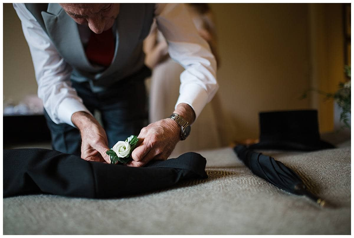 dad of the groom putting on buttonhole bowood hotel golf and spa wedding