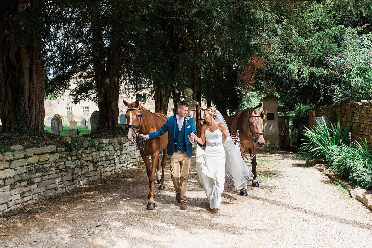 wedding couple walking with horses upcote barn wedding photographer
