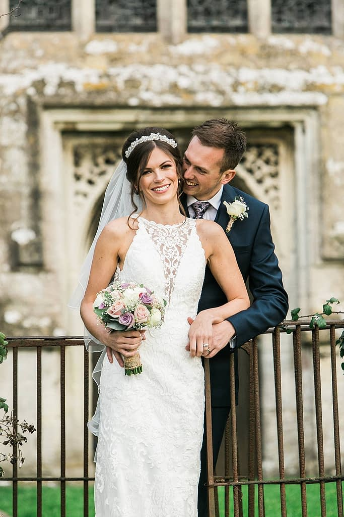 couple cuddle outside church for Gloucestershire wedding photographer
